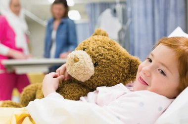 Child hugging a teddy bear in a hospital bed