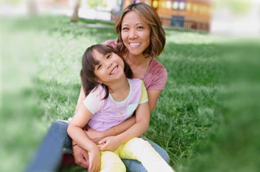 Mother and daughter sitting together in park setting