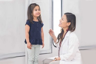 Doctor measuring height of small child