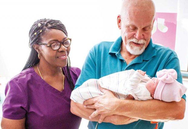 Older man holding a newborn as health care worker looks on