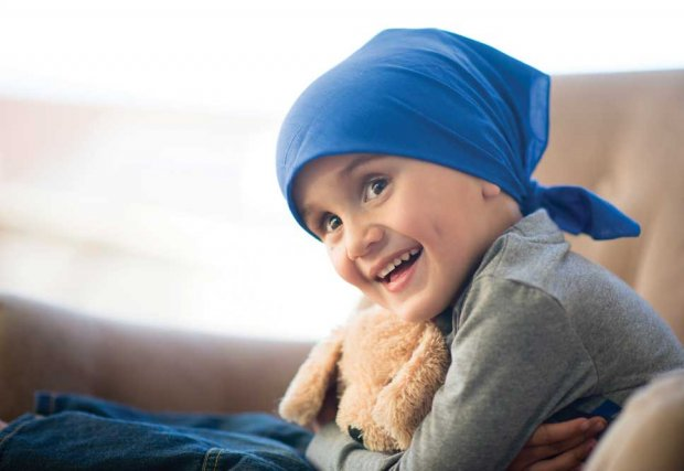 Child cancer patient wearing bandana, smiling holding a teddy bear